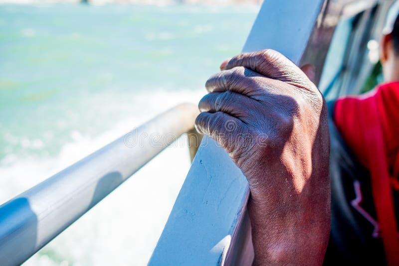 Feche acima da mão emigrante africana fina e magro do homem no barco ao cruzar o mar Mediterrâneo a Europa no dia ensolarado como fotografia de stock