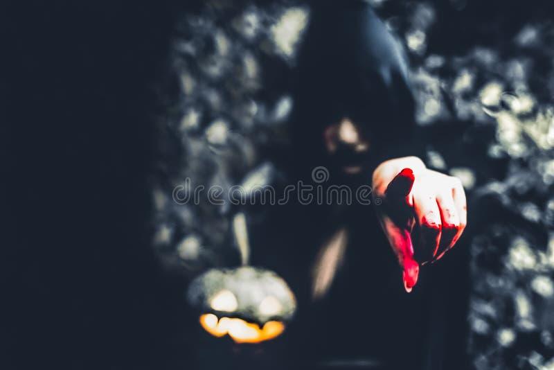 Feche acima da mão ensanguentado do feiticeiro que aponta à parte dianteira La da abóbora fotos de stock