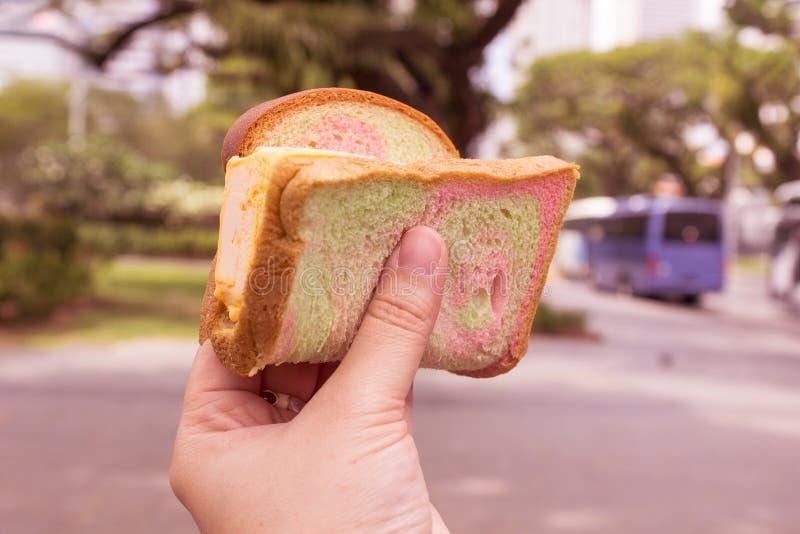 Feche acima da mão esquerda do ` s da mulher que guarda o gelado que o pão cortado envolvido, alimento da rua no parque, ele é fu imagens de stock