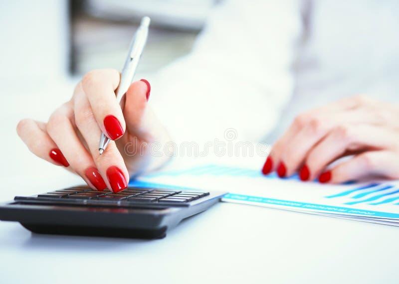 Feche acima da mão fêmea do contador ou do banqueiro que faz cálculos Economias, finanças e conceito da economia imagens de stock royalty free