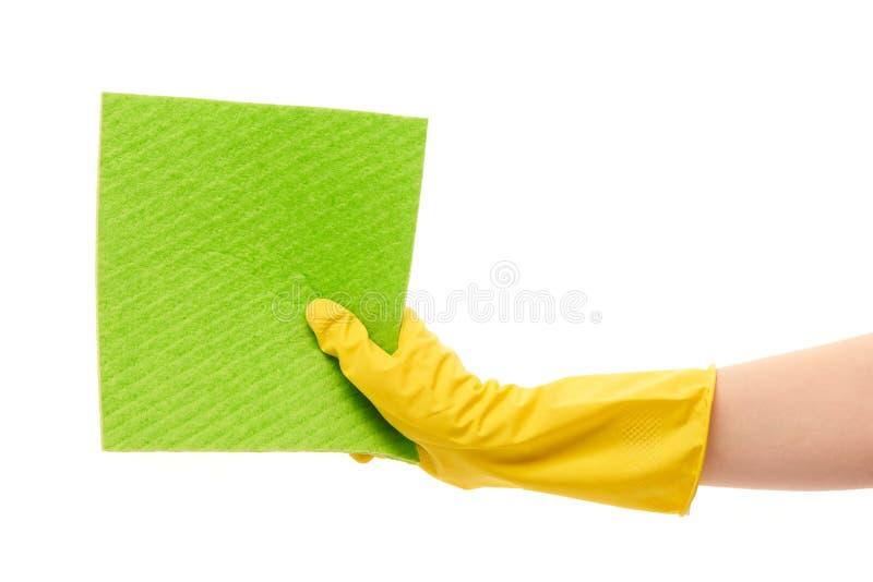 Feche acima da mão fêmea na luva de borracha protetora amarela que guarda o pano verde foto de stock royalty free