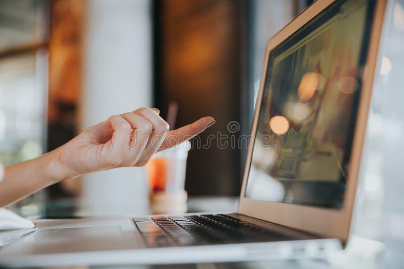 Feche acima da mão fêmea que aponta o dedo à tela do portátil imagem de stock royalty free