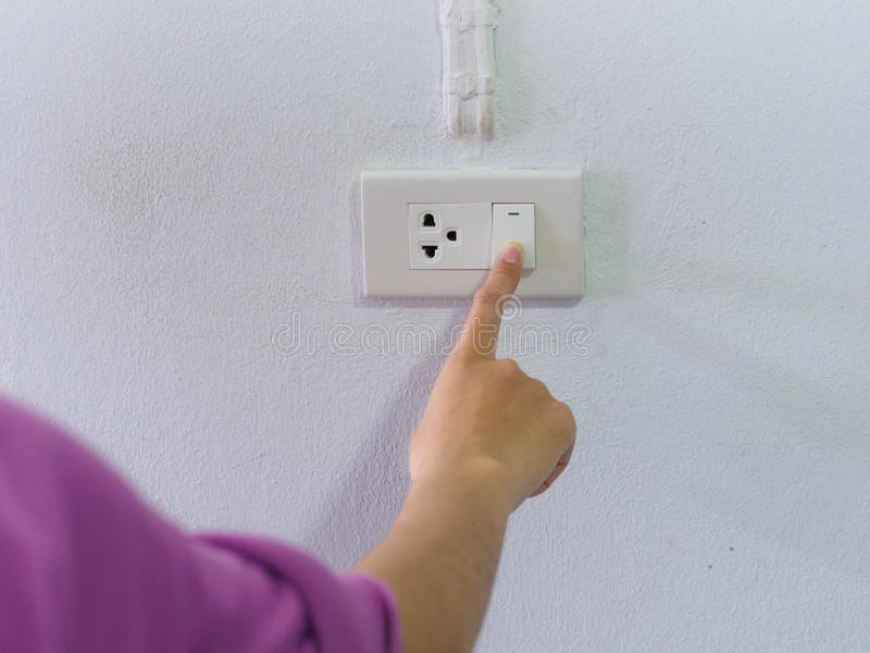 Feche acima da mão fêmea que gira de ligar/desligar no interruptor da luz cinzento com imagens de stock