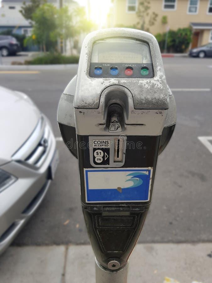 Feche acima da mão fêmea que introduz o cartão de crédito no medidor de estacionamento fotografia de stock