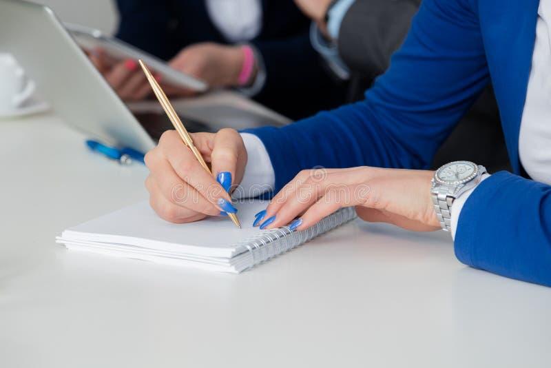 Feche acima da mão fêmea que toma notas em uma reunião de negócios imagens de stock royalty free