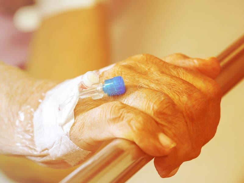 Feche acima da mão idosa paciente do homem da mão com solução salina do iv do intravenous no hospital paciente com a tomada da ag imagens de stock royalty free