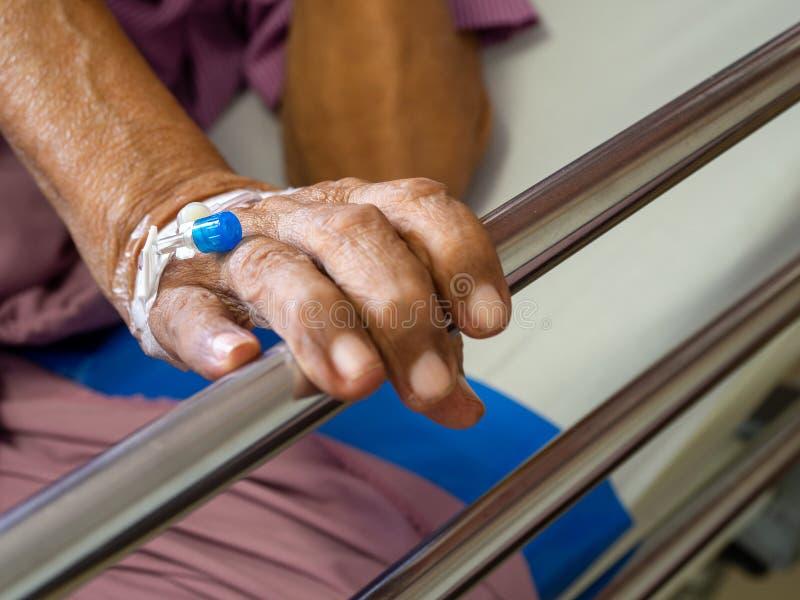 Feche acima da mão idosa paciente do homem da mão com solução salina do iv do intravenous no hospital paciente com a tomada da ag fotografia de stock