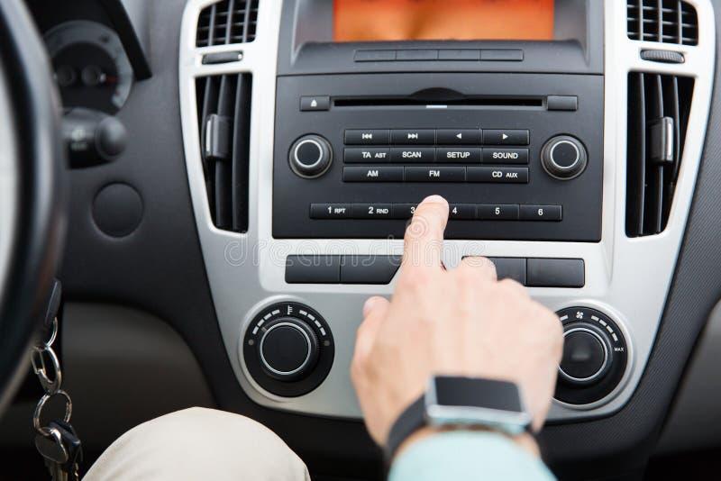 Feche acima da mão masculina que gira sobre o rádio no carro imagem de stock royalty free