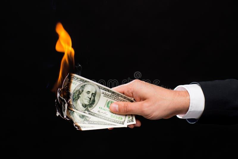 Feche acima da mão masculina que guarda dinheiro ardente do dólar imagens de stock royalty free