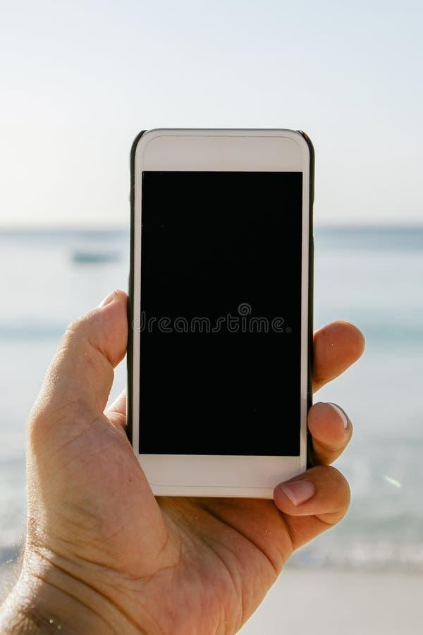 Feche acima da mão masculina que guarda o smartphone com tela vazia imagens de stock