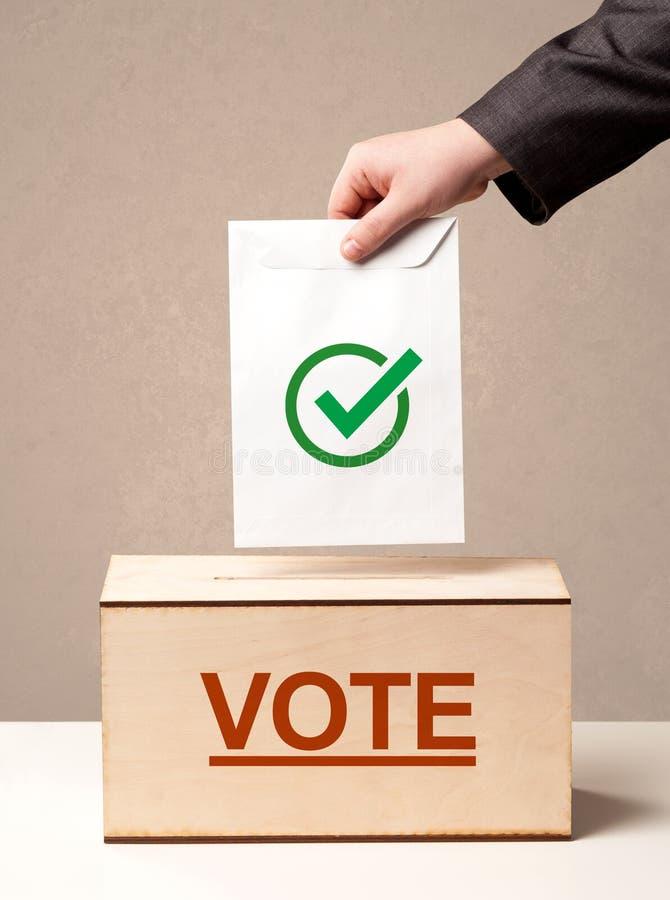 Feche acima da mão masculina que põe o voto em uma urna de voto fotografia de stock