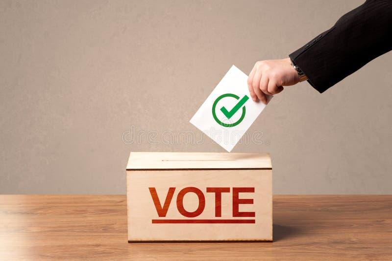 Feche acima da mão masculina que põe o voto em uma urna de voto imagem de stock