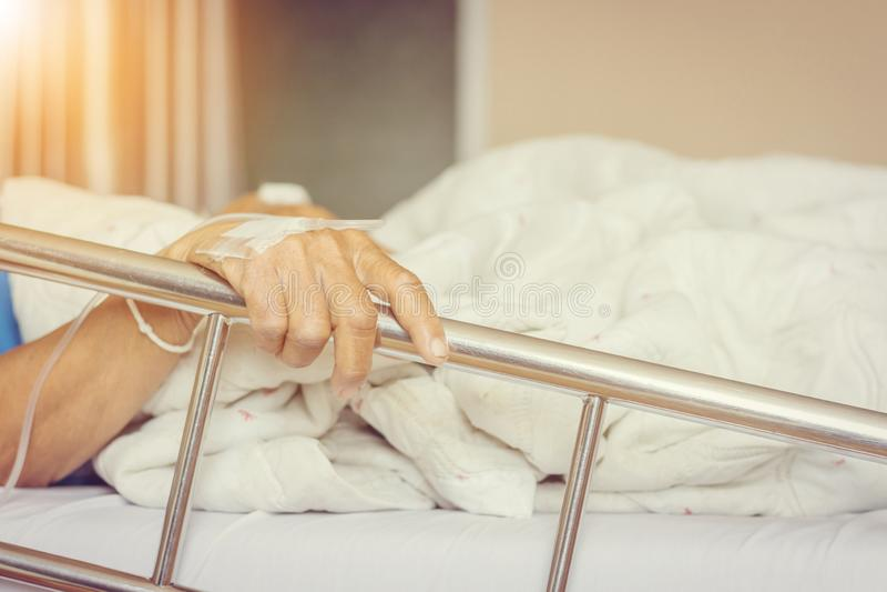 Feche acima da mão paciente do ` s das mulheres idosas asiáticas em um receivi do gotejamento imagens de stock