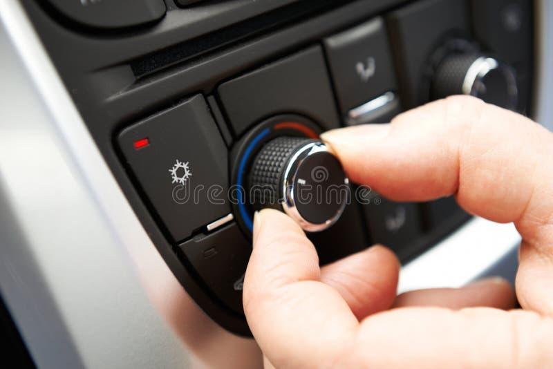 Feche acima da mão que ajusta o controle do condicionamento de ar do carro em Dashb fotos de stock