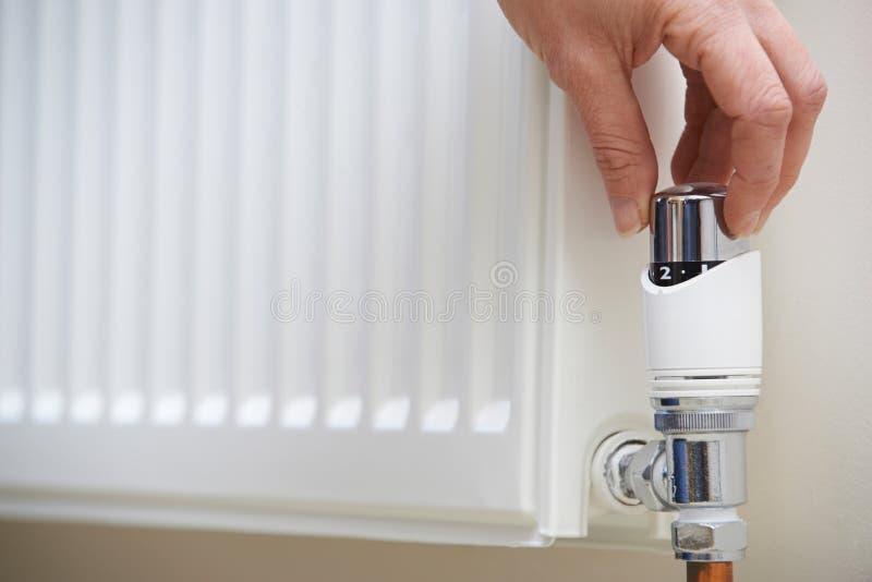 Feche acima da mão que ajusta o termostato do aquecimento imagens de stock
