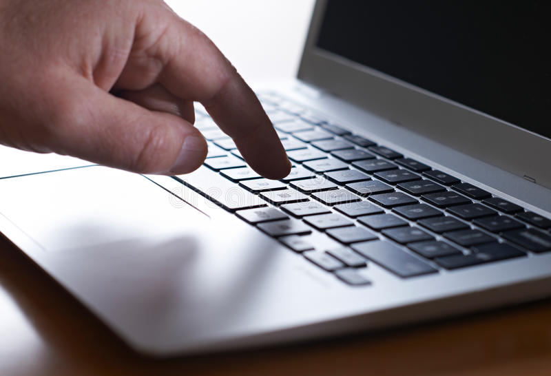 Feche acima da mão que datilografa no teclado do portátil fotografia de stock