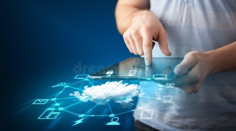 Feche acima da mão que guarda a tabuleta com tecnologia de rede da nuvem foto de stock