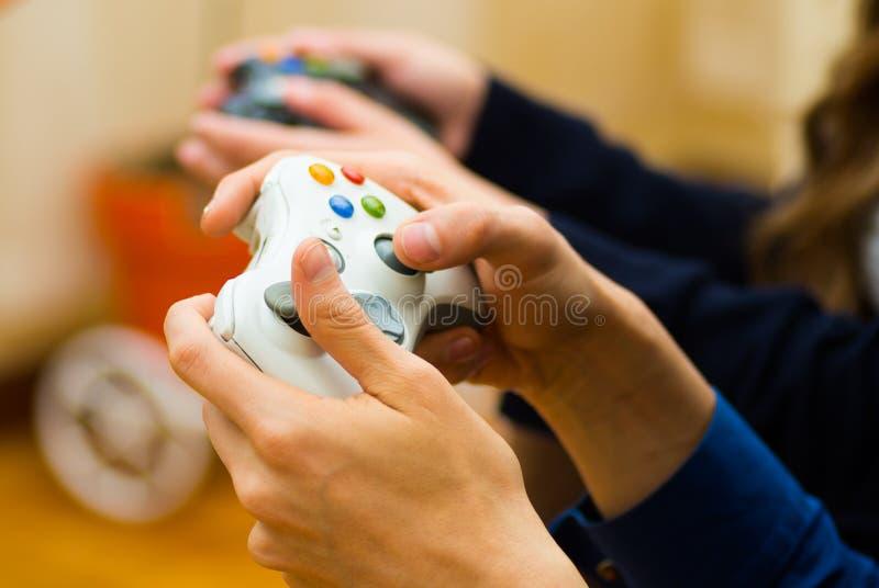 Feche acima da mão que guarda um gamepad para jogar os jogos de vídeo no sofá, conceito sobre o home entertainment, jogos de víde imagens de stock