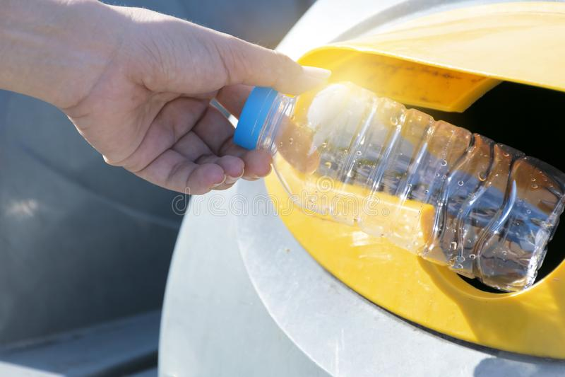 Feche acima da mão que joga a garrafa plástica vazia no lixo foto de stock royalty free