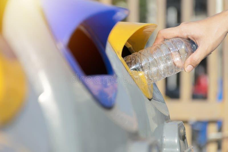 Feche acima da mão que joga a garrafa plástica vazia no lixo que recicla o conceito imagens de stock royalty free