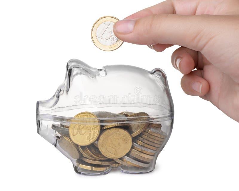 Feche acima da mão que põe a moeda no mealheiro fotografia de stock royalty free