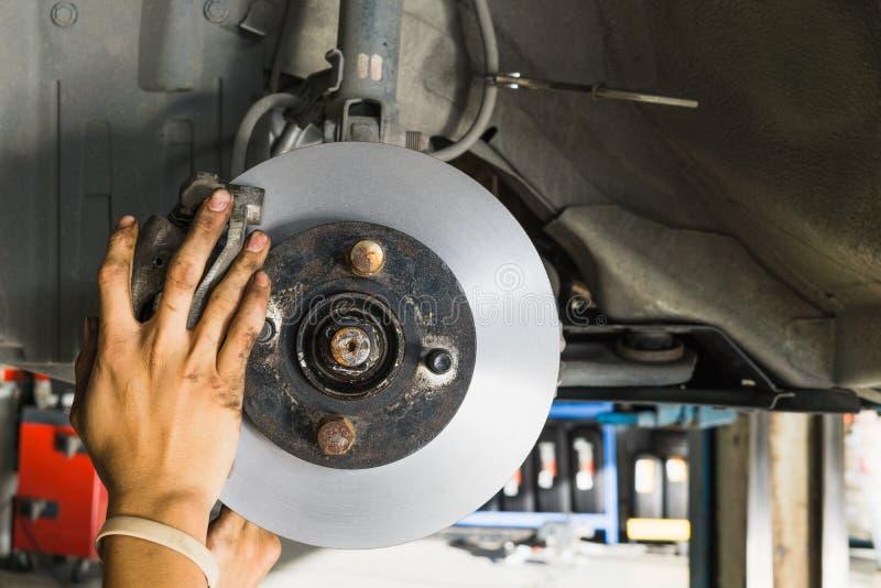 Feche acima da mão que substitui freios de disco novos do carro levantado foto de stock