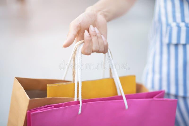 Feche acima da mão da terra arrendada da jovem mulher da consumição muita o saco de compras no boutique da forma após ter comprad fotografia de stock royalty free