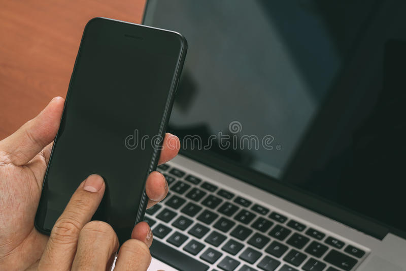 feche acima da mão usando o telefone esperto, portátil, pagamento da operação bancária em linha fotos de stock royalty free