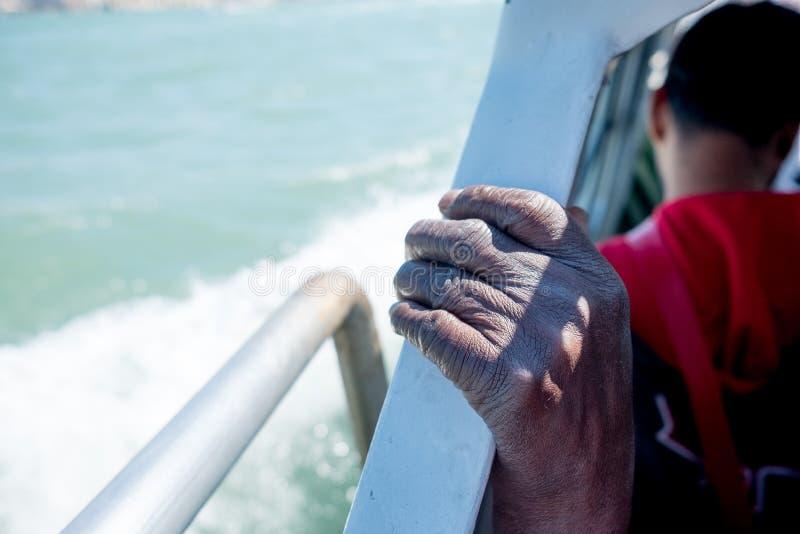 Feche acima da m?o emigrante africana fina e magro do homem no barco ao cruzar o mar Mediterr?neo a Europa no dia ensolarado foto de stock