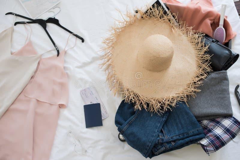feche acima da mala de viagem com vestidos, chapéu de palha, passaporte imagem de stock royalty free