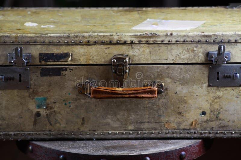 Feche acima da mala de viagem usada velha isolada com rebites, o aperto de couro e os fechamentos de combinação foto de stock royalty free