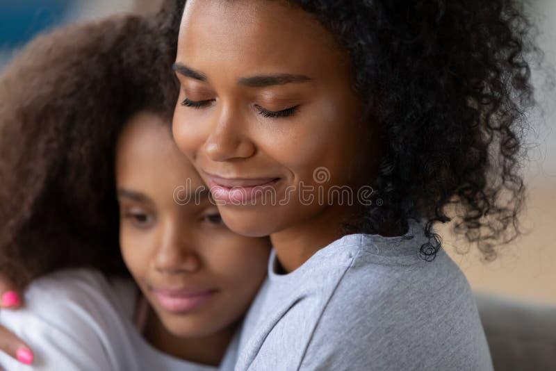 Feche acima da mamã preta que abraça a filha adolescente fotografia de stock royalty free