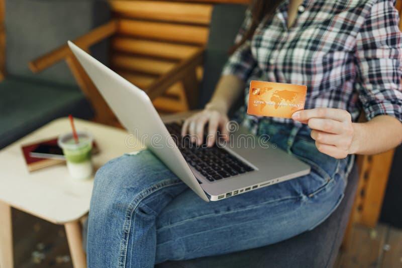 Feche acima da menina colhida no funcionamento de assento no computador do PC do portátil, crédito bancário do café de madeira da foto de stock