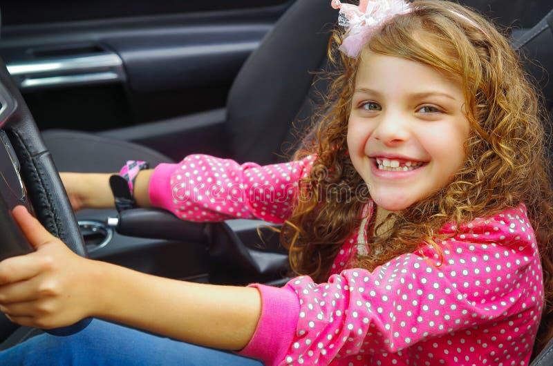Feche acima da menina de sorriso bonita pequena que senta-se no carro que finge conduzir o carro preto luxuoso, weaing um rosa imagens de stock royalty free