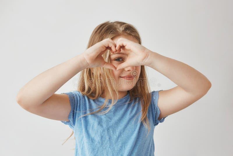 Feche acima da menina loura bonita que faz o coração com mãos, olhando através dele in camera, levantando para a foto com sorriso fotografia de stock royalty free