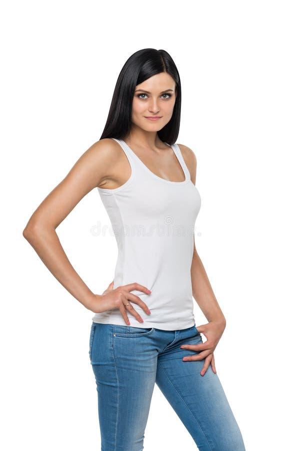 Feche acima da menina moreno nas sarjas de Nimes e na camiseta de alças branca fotos de stock