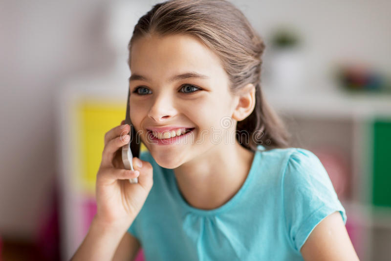 Feche acima da menina que chama o smartphone em casa imagem de stock royalty free