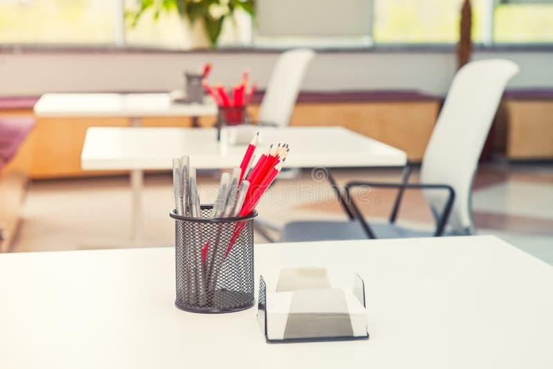 Feche acima da mesa com suporte focalizado com artigos de papelaria, penas e lápis com fundo borrado do escritório vazio claro mo imagens de stock royalty free