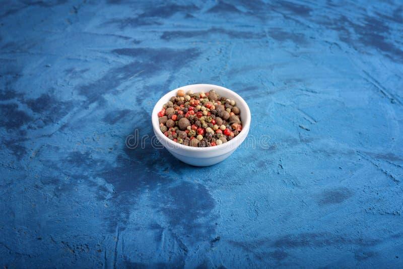 Feche acima da mistura de pimentas em um potenciômetro contra um fundo de pedra azul spice foto de stock royalty free