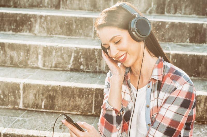 Feche acima da moça alegre com os fones de ouvido que relaxam foto de stock royalty free