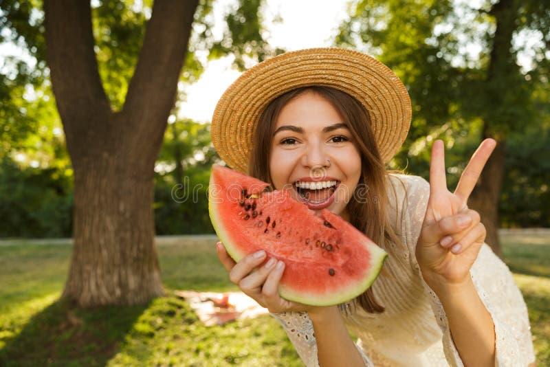 Feche acima da moça alegre no tempo da despesa do chapéu do verão no parque fotos de stock