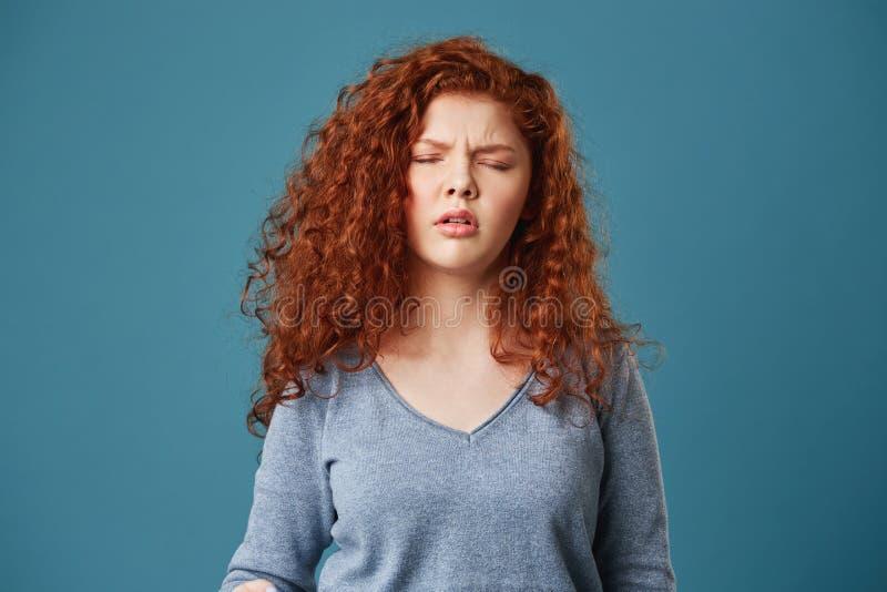 Feche acima da moça bonita com cabelo e as sardas ondulados do gengibre na camisa cinzenta que tem a dor de cabeça após a noite s foto de stock