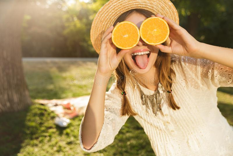 Feche acima da moça de sorriso no tempo da despesa do chapéu do verão no parque, mostrando o orangotango cortado fotos de stock royalty free