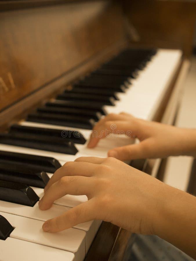 Feche acima da moça que joga o piano em casa foto de stock