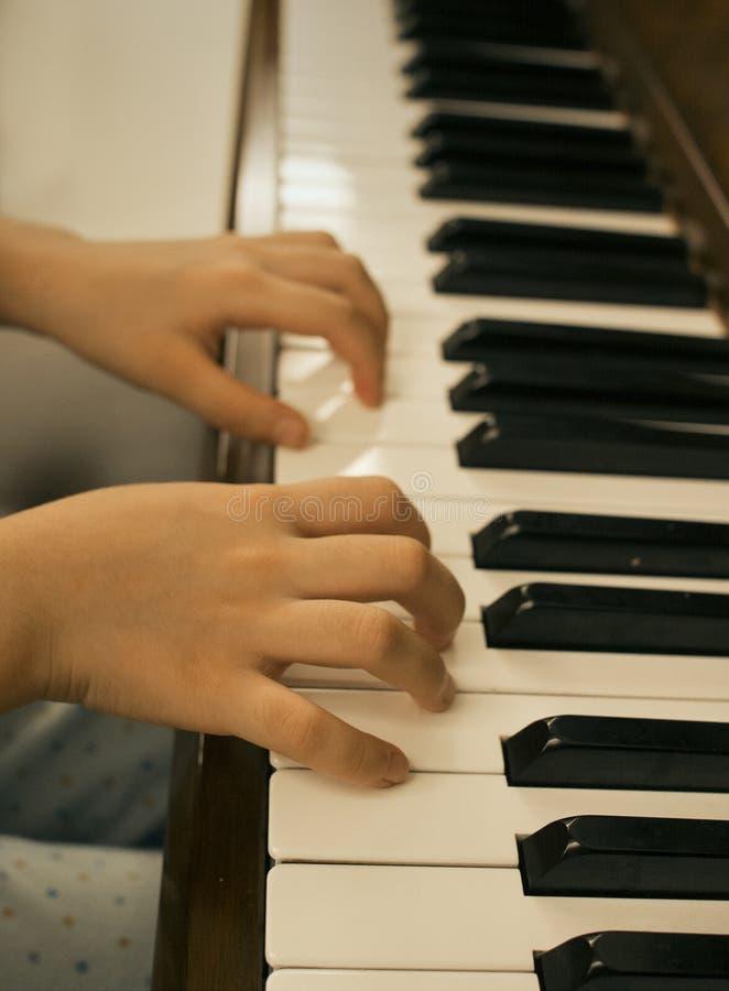 Feche acima da moça que joga o piano em casa imagens de stock