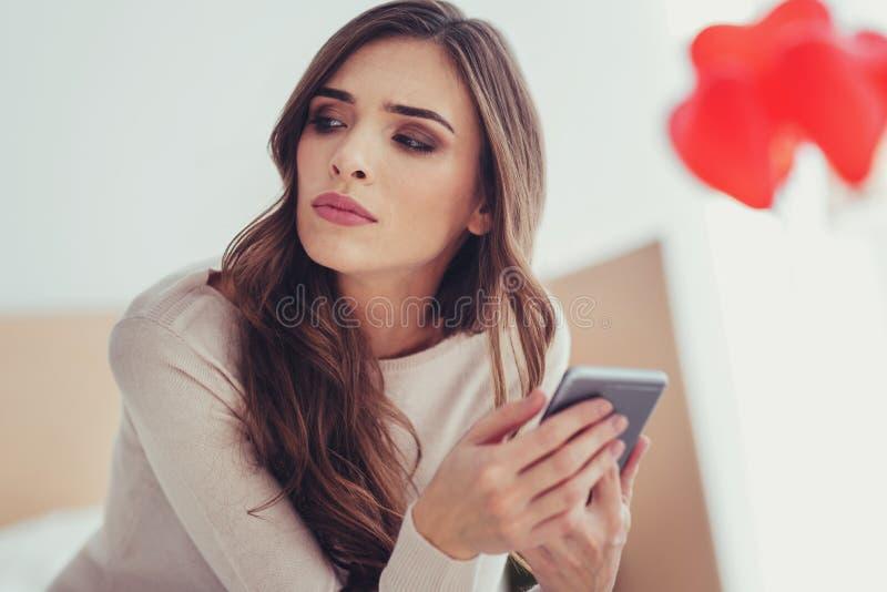 Feche acima da moça que olha afastado com um telefone celular nas mãos fotos de stock