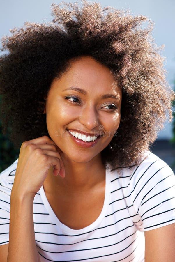 Feche acima da mulher africana nova com o cabelo encaracolado que olha ausente e que sorri fora imagens de stock
