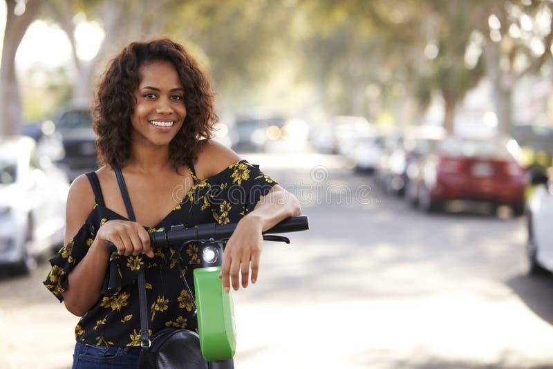 Feche acima da mulher afro-americano milenar que inclina-se em um 'trotinette' elétrico na rua, sorrindo à câmera foto de stock