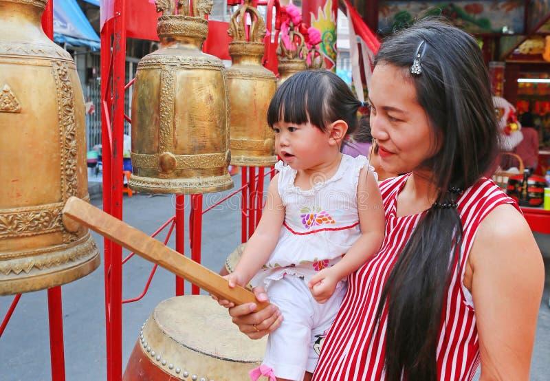 Feche acima da mulher asiática e o seu cilindro e sino da batida do daugther no festival chinês do ano novo fotos de stock royalty free