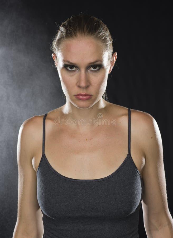 Feche acima da mulher atlética que olha feroz na câmera imagem de stock
